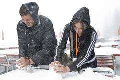 Jovo, links, und Biljana bauen aus Schnee einen kleinen Schneemann auf einem Tisch auf der Schwägalp. (Bild: Keystone)