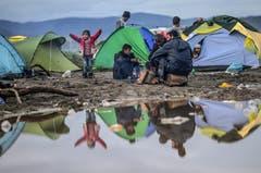 Aufgrund der Regenfälle haben sich in Idomeni Pfützen gebildet und der Boden ist schlammig. Viele Flüchtlinge haben ihre Zelte abgebrochen und auf trockeneren Flecken wieder aufgebaut. (Bild: Keystone)