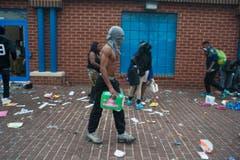 Ein Rebell und seine Trophäe: Die Demonstrationen wurden genutzt, um Geschäfte zu plündern. (Bild: Keystone/EPA/Noah Scialom)