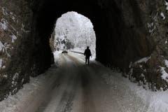 Winter auf dem Balkan: In der Nähe von Sarajewo geht ein Mann auf der verschneiten Strasse durch einen Tunnel. (Bild: AP Photo/Amel Emric)