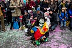 Eine als Hexe kostümierte Person und ein Kind liegen in den farbigen Konfetti am Boden umringt von Zuschauern. (Bild: ENNIO LEANZA)