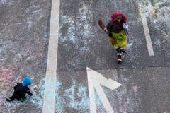 """Eine als Hexe kostümierte Person läuft am Umzug """"ZüriCarneval 2015"""", während ein Kind auf der Strasse mit Konfetti spielt. (Bild: ENNIO LEANZA)"""