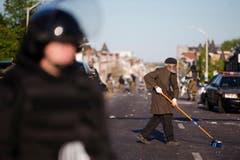 Am Dienstag wischt ein älterer Mann die Strasse. (Bild: AP Photo/Matt Rourke)