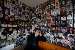 Sonntag, 20. MNärz: Die Bosnierin Habiba Masc vor den Bildern von Opfern des MAssakers von Srebrenica im Sommer 1995. Sie verlor damals ihren Mann Sadija und ihren Sohn Sadmir. (Bild: AP Photo / Amel Emric)