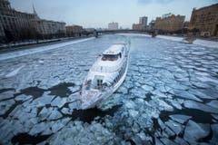 Auf dem Fluss Moskwa durch die russische Metropole Moskau hat ein Touristenboot mit harten Brocken zu kämpfen. Das Wasser gefriert bei Lufttemperaturen von -18 Grad. (Bild: AP Photo/Alexander Zemlianichenko)