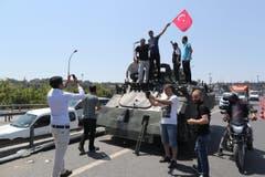 Die Menschen posieren vor einem Militärpanzer in Istanbul am Samstag. (Bild: EPA/TOLGA BOZOGLU)
