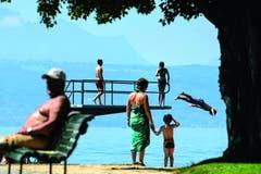 Laurent Gillieron - 3. Platz Kategorie «Alltag», 2013 kam der Sommer zuerst gar nicht - und wurde dann umso heisser. Am 27. Juli springt ein Mann in der Lausanner Badeanstalt Bellerive in den Genfersee. Im Hintergrund sind die französischen Alpen zu sehen. (Bild: Swiss Press Photo / Laurent Gillieron)