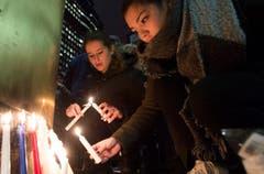 Frauen zünden Kerzen an vor der französischen Botschaft im Montreal. (Bild: AP/Graham Hughes)