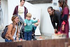 Mami Nicole und Eelis Dettwiler aus Knonau versuchen, mit der Metallkugel die Eier zu treffen. (Bild: Maria Schmid / Neue ZZ)