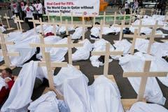 Die Demonstration gegen die schlechten Bedingungen auf den Baustellen in Katar ist augenfällig: Die Aktivisten mimen Tote. (Bild: KEYSTONE/ENNIO LEANZA)