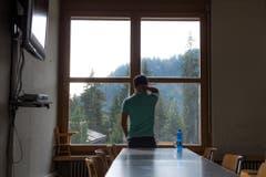 Im Speisesaal beobachtet ein Asylsuchender das Treiben auf dem Vorplatz. (Bild: Dominik Wunderli)