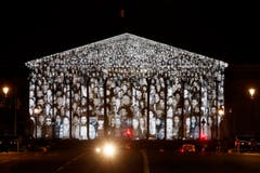Der französische Künstler JR und der US-amerikanische Filmemacher Darren Aronofsky lassen Gesichter am französischen Parlamentsgebäude erstrahlen. (Bild: EPA / Yoan Valat)