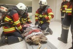 Eine ohnmächtige Frau wird von der Feuerwehr mit der Rettungsliege aus dem Schwimmbad befördert. (Bild: Edi Ettlin)