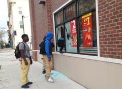 Hier gehts zur Selbstbedienung: Leute klettern durch ein Fenster in ein Geschäft. (Bild: AP / Juliet Linderman)