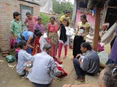 """Ruth und Walter Odermatt brachten gesammelte Kleider in ein Dorf etwa eine Stunde südlich von Kathmandu. Im Dorf, das von 8 Familien bewohnt ist, kam nur wenig Hilfe der Hilfswerke an. Rechts sitzt """"Buddhi"""" und nimmt die Adressen der Familien auf. (Bild: Walter Odermatt)"""