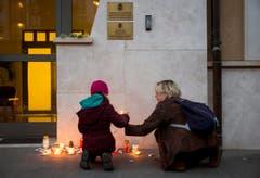 Eine Frau und ein Kind stellen eine Kerze vor die belgische Botschaft in Budapest. (Bild: Balazs Mohai/MTI via AP)