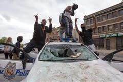 Jugendliche und ein zerstörtes Polizeifahrzeug. (Bild: EPA/ Michael Reynolds)