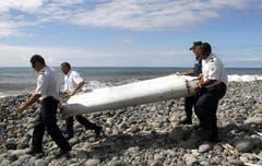 Polizisten bringen das gefundene Wrackteil weg. Ergebnisse seiner Untersuchung sollen in zwei Tagen vorliegen. (Bild: Keystone)