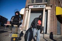 Szene nach den Unruhen: Ein Polizist hält Wache, ein Mann trägt den Abfall weg. (Bild: Keystone / EPA / John Taggart)