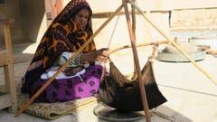 Hier wird traditionell die Butter durch Schütteln in einem Ziegenfell hergestellt. (Bild: Omanifrau bei der Herstellung von Butter in einem Ziegenfell)