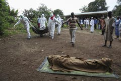 Liberische Krankenhelfer und Ärzte tragen ein Ebola-Opfer. Dieses soll in der Banjor Community am Rande von Monrovia beerdigt werden. (Bild: Keystone)
