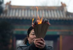 Andächtig verbrennt eine Gläubige Weihrauch. (Bild: Keystone)