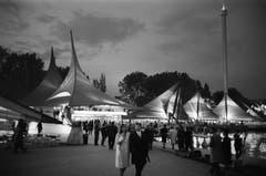 Besucher flanieren an der Expo 64 in Lausanne über das Gelände: Neben Ausstellungszelten ist rechts der markante Aussichtsturm, genannt die Spirale, zu sehen. (Bild: Keystone / Str)