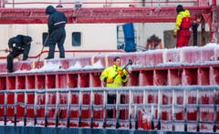 Seeleute befreien im Hafen von Wismar in Norddeutschland den dänischen Frachter «Vestfjord» von Eis. (Bild: EPA/JENS BUETTNER)
