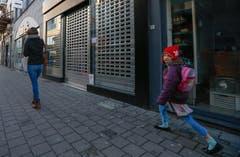 Sie wollte eigentlich in die Schule: Ein Schulkind (mit Schweizer Kappe) geht wieder heim. (Bild: EPA/ Laurent Debrule)