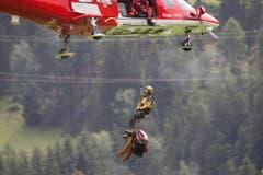 Ein Rega-Helikopter fliegt einen Retter und Bergungsmaterial vom Unglücksort im Beriech der Kirche St. Peter Mistail zum Umladeplatz in Tiefencastel. (Bild: Keystone)