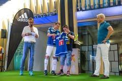 Claudio Lustenberger (2. von links) überreicht dem Gewinner (3. von links) des Spruchwettbewerbes ein neues Heimtrikot. Der Spruch «Veni Vidi Vici»steht auf der Etikette. (Bild: Roger Grütter / Neue LZ)