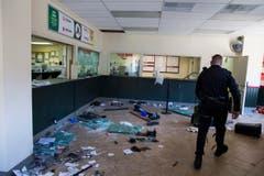 Ein Polizist in einem zertrümmerten Geschäft. (Bild: Keystone / Evan Vucci)