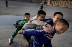 Nordkoreanische Jungs versuchen sich während des Inlineskatens zu fangen und brechen dabei in Gelächter aus. (Bild: Keystone)