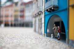 Die Piazza wird belebt: Eine Kleinfamilie mit Hund under den Bögen eines Hauses. (Bild: Gabriele Putzu/Ti-Press/Keystone)