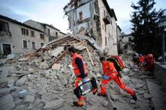 Helfer suchen in Arcuata del Tronto nach Verschütteten. (Bild: AP / Sandro Perozzi)