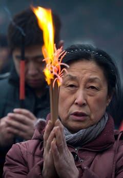 Andächtig betet eine Chinesin, während sie Weihrauch abbrennt. (Bild: Keystone)