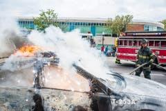 Ein brennendes Polizeiauto wird gelöscht. (Bild: Keystone/EPA/Noah Scialom)