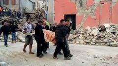 Helfer bergen eines der Opfer in Amatrice. (Bild: AP Photo / Videostill)