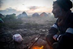 Ein Mann wärmt sich an einem Feuer im Aufnahmelager in Idomeni an der griechisch-mazedonischen Grenze. (Bild: Keystone)