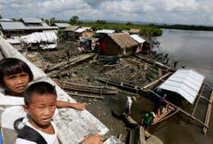 Zwei philippinische Schulkinder vor den zerstörten und notdürftig wieder aufgebauten Hütten in ihrem Dorf in der östlichen Provinz Samar. (Bild: Keystone)