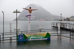 Ein junger Mann balanciert bei starkem Regen am Ufer des Luganersees. (Bild: Keystone)