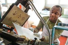 Nduka Anaenyonu alias «Charlie» arbeitet an der Backmaschine. Gut auf der Presse zu sehen sind die Muster, die den Hostien das wunderbare Aussehen verleihen. (Bild: Dominik Wunderli / Neue LZ)