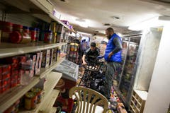 Helfer räumen in einem geplünderten Geschäft auf. (Bild: Keystone / Evan Vucci)