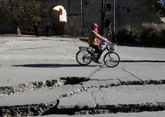 A man rides a bicycle past cracks in a road in Norcia, central Italy, after an earthquake with a preliminary magnitude of 6.6 struck central Italy, Sunday, Oct. 30, 2016. Central Italy was hit by another powerful earthquake Sunday, toppling buildings that had recently withstood other major quakes and sending panicked residents back into the streets, but causing no immediate loss of life. (AP Photo/Gregorio Borgia) (Bild: Keystone)