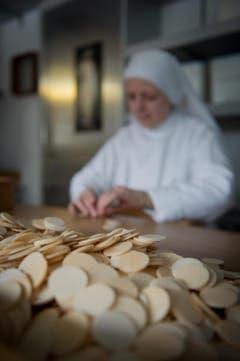Im Schwyzer Frauenkloster St. Peter wird für eine bessere Welt gebetet und gebacken. Im Bild Sr. Margarita bei der Endkontrolle der Hostien. (Bild: Pius Amrein / Neue LZ)