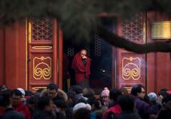 Ein Mönch bei einem Tempel, während Gläubige beten. (Bild: Keystone)