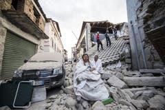 Bewohner von Amatrice auf den Trümmern ihrer Häuser. (Bild: EPA / Massimo Percossi)