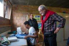 Besucher Oskar Stockmann interessiert sich für einen jungen Asylsuchenden, der Hosen an der Nähmaschine flickt. Begegnungs- und Gestaltungsraum können Asylsuchende unter anderem Zeichnen, Schneidern oder sich gegenseitig die Haare schneiden. (Bild: Dominik Wunderli)