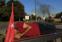 Ein Demonstrant schläft vor dem rauchenden Militärhauptquartier in Ankara. (Bild: AP Photo/Ali Unal)