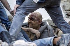 Ein verletzter Mann wird in Amatrice aus den Trümmern geborgen. (Bild: EPA / Massimo Percossi)